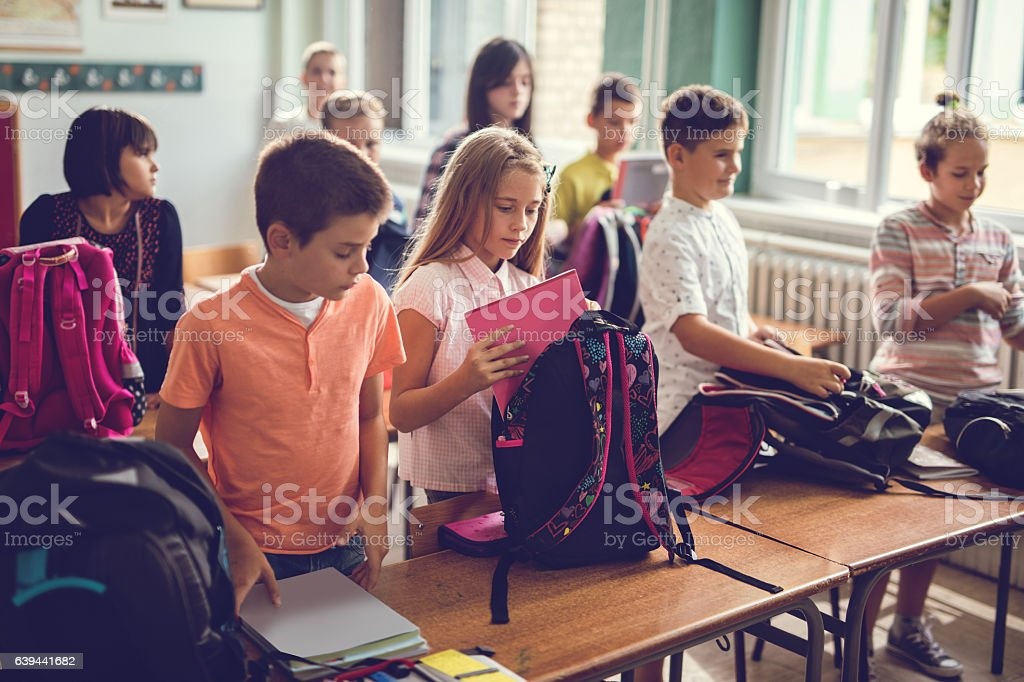 Group of elementary students packing their backpacks after the classroom. stock photo