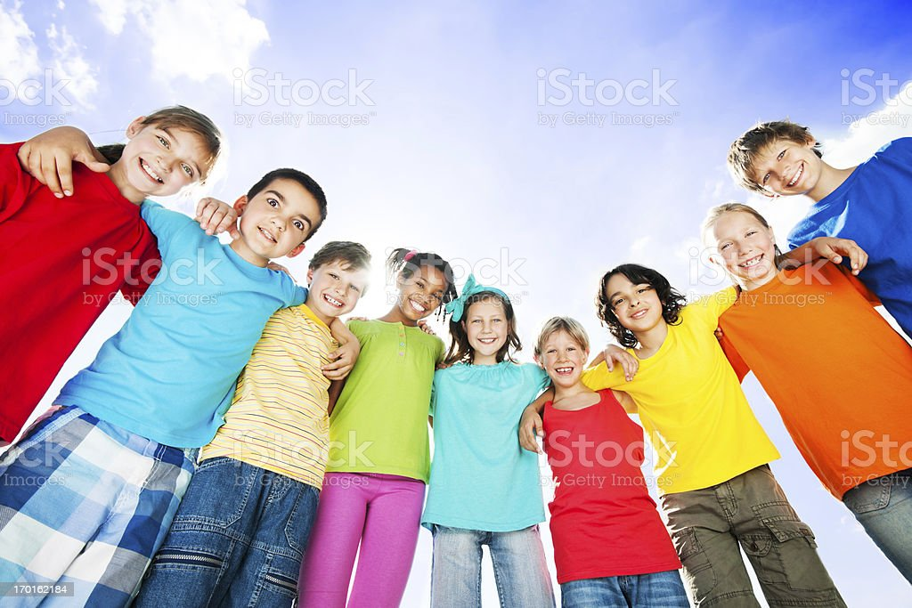 Group of embraced cheerful kids against the sky. royalty-free stock photo