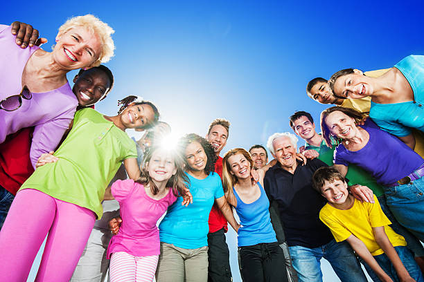 Group of embraced people standing against blue sky. stock photo