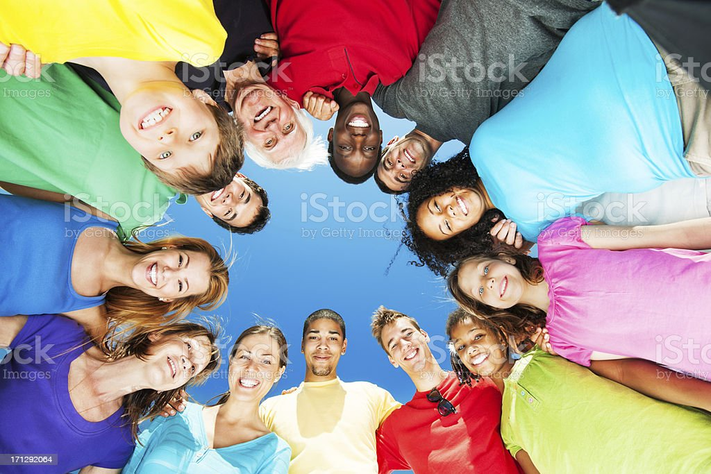 Gruppe von selbstverständlich Personen stehen im Kreis gegen blauen Himmel. – Foto