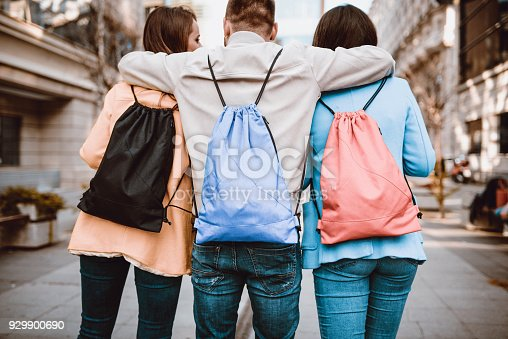 872670290istockphoto Group of Embraced Students with Backpacks Walking After School 929900690