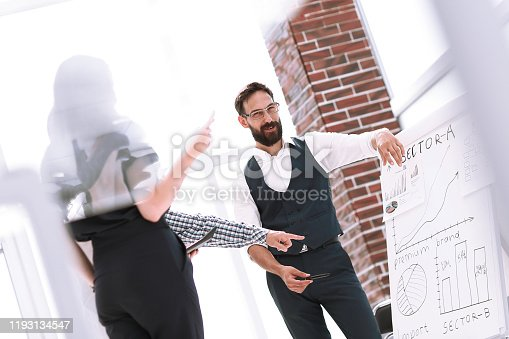 618851838 istock photo group of employees discussing financial performance while standing in the office 1193134547