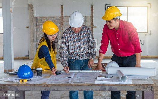 521012560 istock photo Group of engineer checking the blueprint on the table and talking about construction project with commitment to success at construction site 926518110