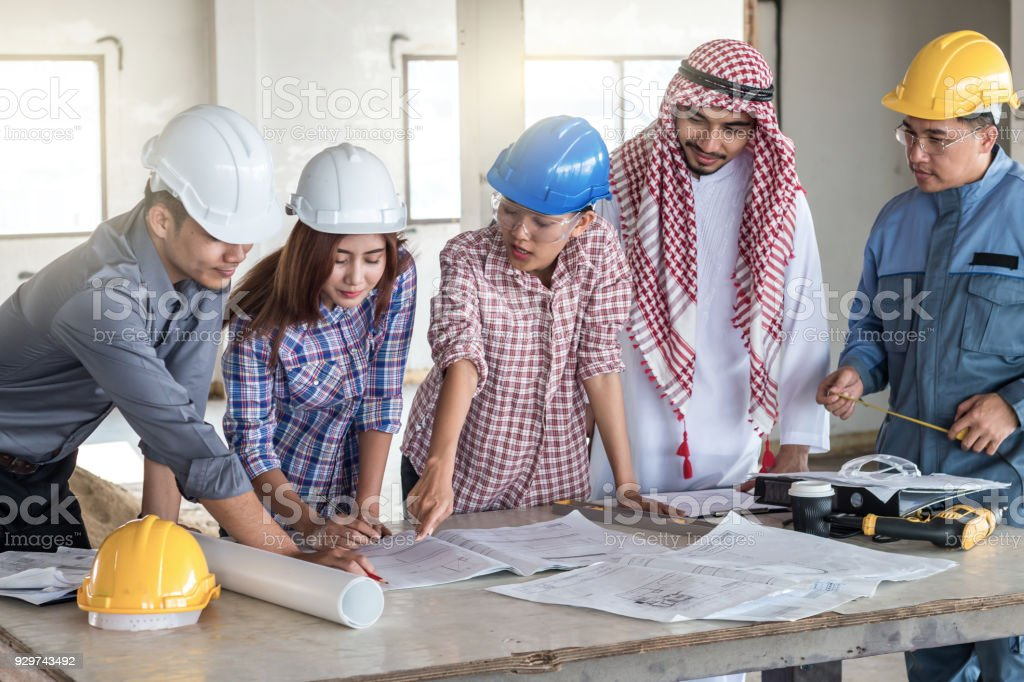 Group of engineer checking the blueprint on the table and talking group of engineer checking the blueprint on the table and talking about construction project with commitment malvernweather Images