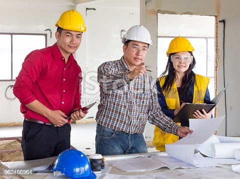 681142982 istock photo group of engineer/architect/worker man and woman discussing about building plan for construction at job site, working on desk/table with drawing/blueprint/business plan 962466964