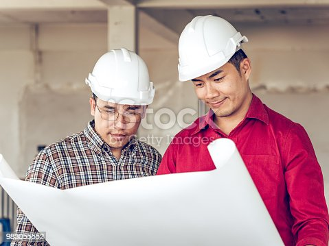 681142982 istock photo Group of engineer/architect/worker man and woman discussing about building plan for construction at job site, working on desk/table with drawing/blueprint/business plan 983055552