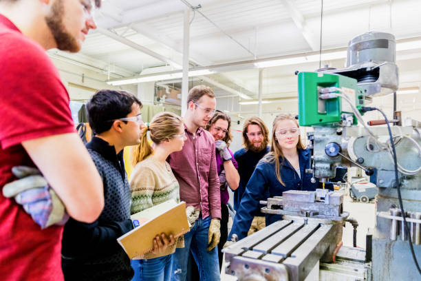 Group of Engineering Students Observing the Senior Student Operating a Heavy Machinery stock photo
