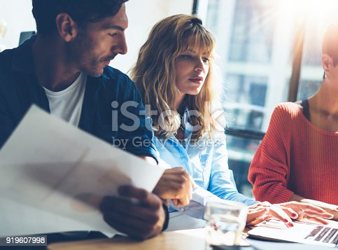 912617272 istock photo Group of entrepreneurs are looking for a business solution during work process at sunny office.Young blonde woman using laptop.Blurred background.Horizontal.Cropped. 919607998