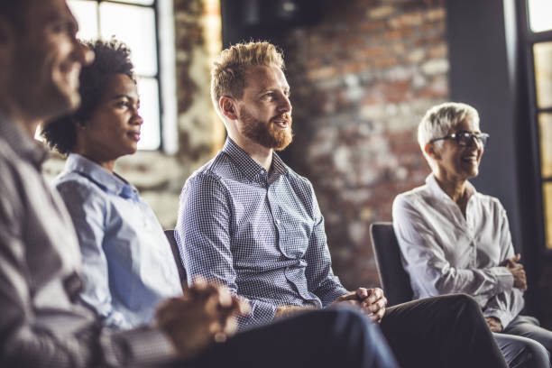 Group of entrepreneurs attending a business seminar in a board room. Business people sitting on an education event in a board room. Focus is on redhead man. group therapy stock pictures, royalty-free photos & images