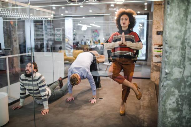 gruppe von unternehmern im casual büro trainieren. - yoga fürs büro stock-fotos und bilder
