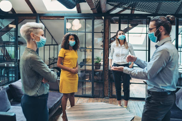 Group of entrepreneurs wearing masks and standing at a distance stock photo
