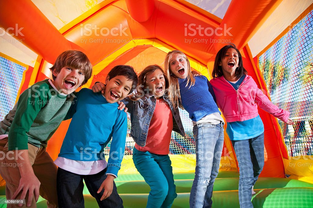 Group of excited children in bouncy house stock photo
