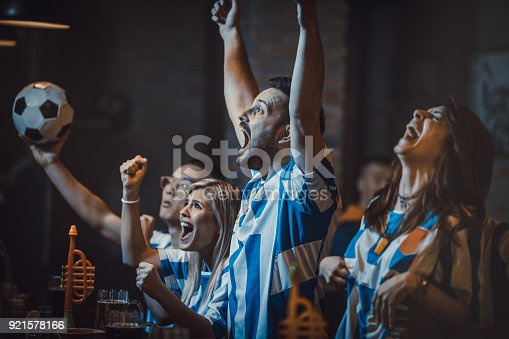 Young cheerful soccer fans celebrating victory of their team in a bar. Focus is on man.