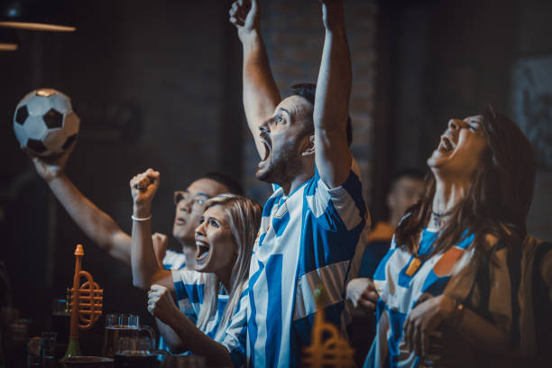 Group of excited soccer fans watching successful game on a TV in a bar. stock photo