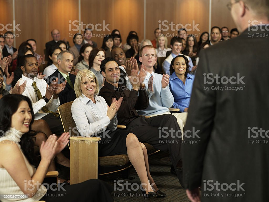 Group of executives applauding for man leading seminar in auditorium royalty-free stock photo