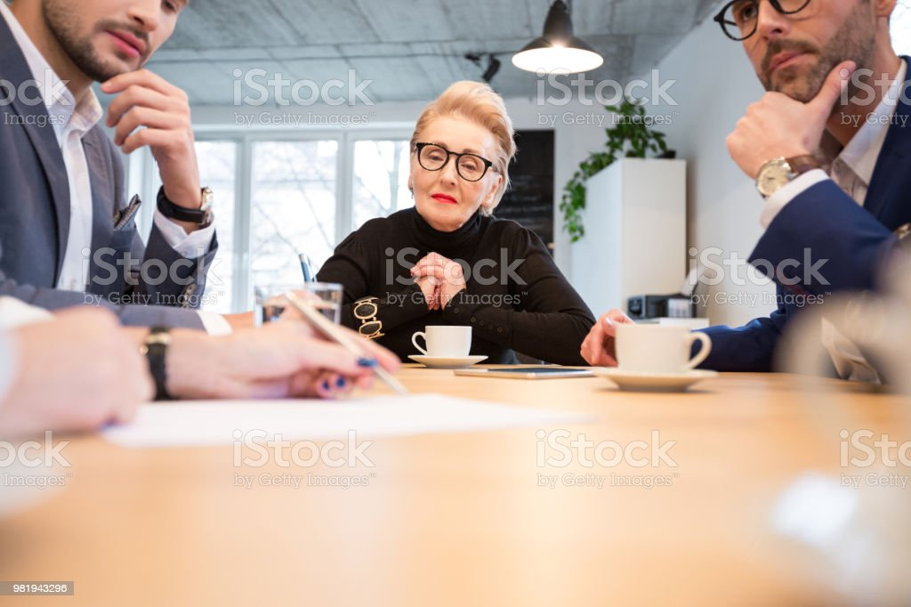 Group of executives discussing during a meeting Group of executives discussing during a meeting. Business people looking at female colleague reviewing a document in boardroom. Active Seniors Stock Photo