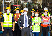istock Group of factory worker wearing a surgical mask. 1267050470