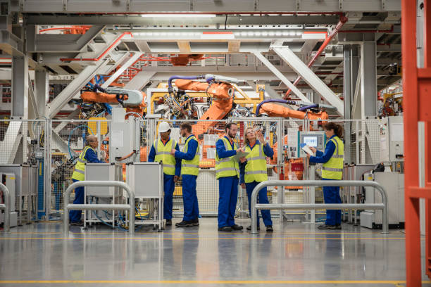 group of factory workers - robotics manufacturing stock photos and pictures