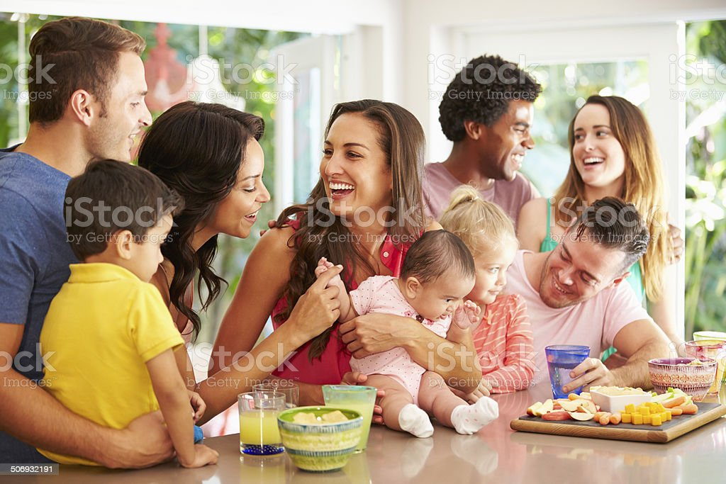 Group Of Families Enjoying Snacks At Home stock photo