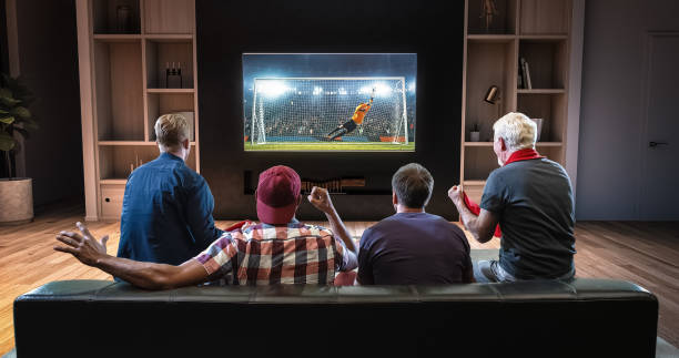 group of fans are watching a soccer moment on the tv and celebrating a goal, sitting on the couch in the living room. - televisor imagens e fotografias de stock