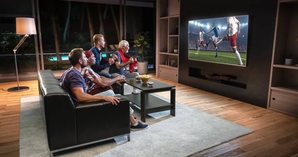 group of fans are watching a soccer moment on the tv and celebrating a goal, sitting on the couch in the living room. - soccer competition stock photos and pictures
