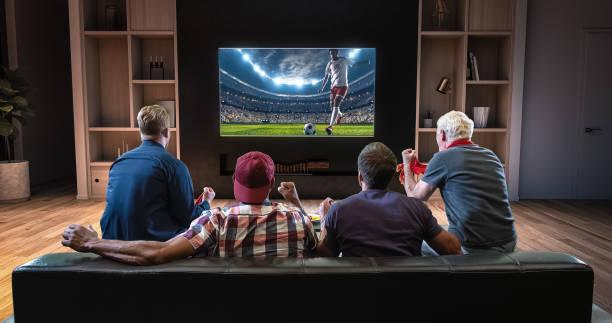 gruppe von fans beobachten fußball kurz auf den fernseher und feiert ein ziel, auf der couch im wohnzimmer sitzen. - fußball themenzimmer stock-fotos und bilder