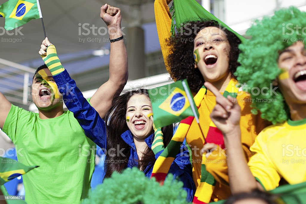 Group of fans cheering for Brazil during a football match. royalty-free stock photo