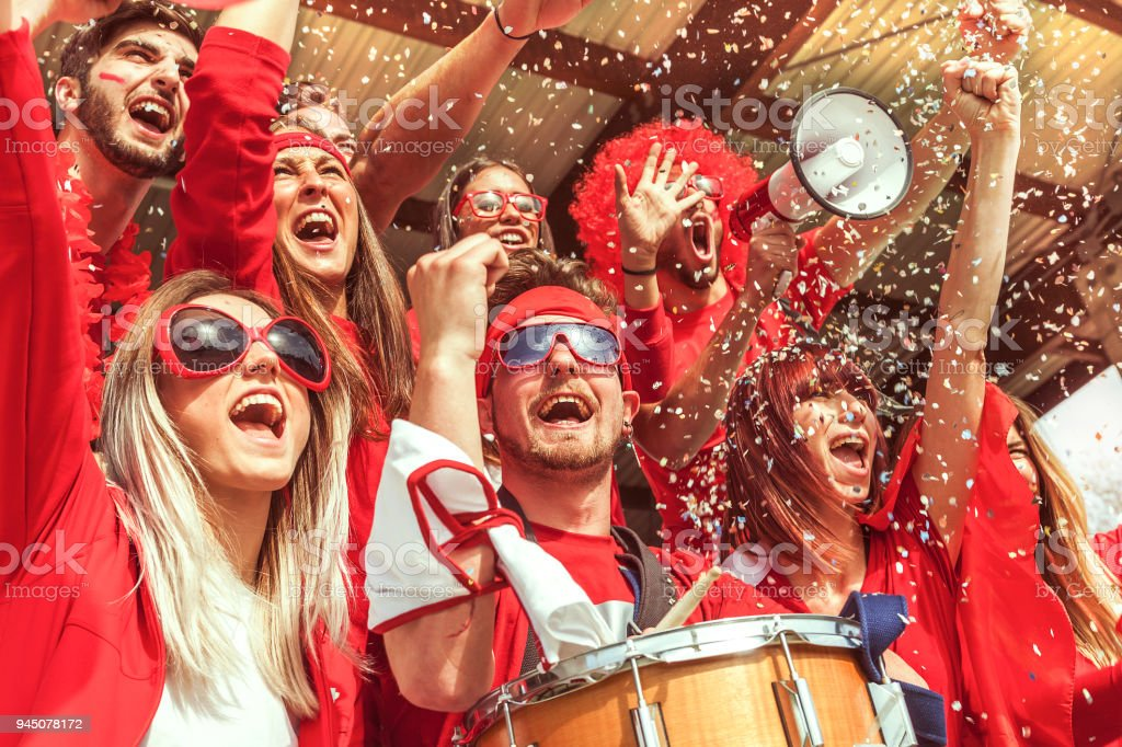 group of fans dressed in red color watching a sports event - Royalty-free 20-29 Years Stock Photo