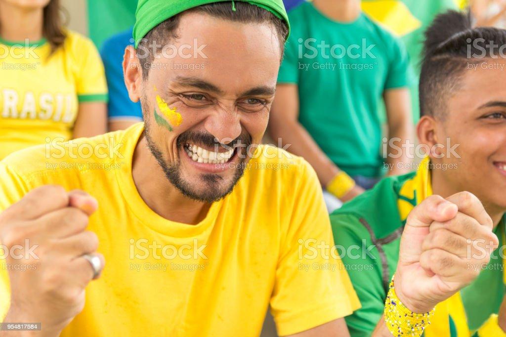 Grupo de fãs assistindo a uma partida e torcer pela equipa brasileira. - foto de acervo