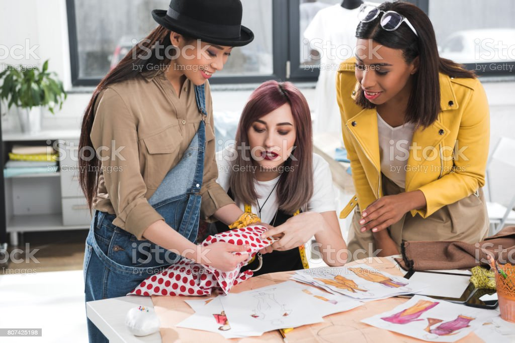 group of fashion designers together working on project in clothing store stock photo