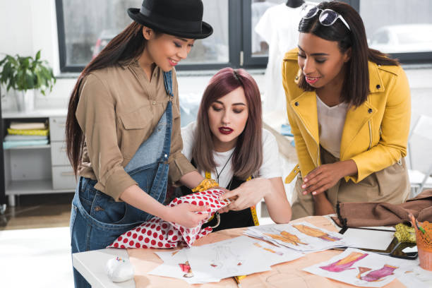 group of fashion designers together working on project in clothing store group of fashion designers together working on project in clothing store fashion designer stock pictures, royalty-free photos & images