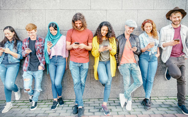 group of fashion friends watching on their smart mobile phones - millennial generation z addicted to new technology trends - concept of people, tech, social media, friendship and youth lifestyle - религиозная одежда стоковые фото и изображения