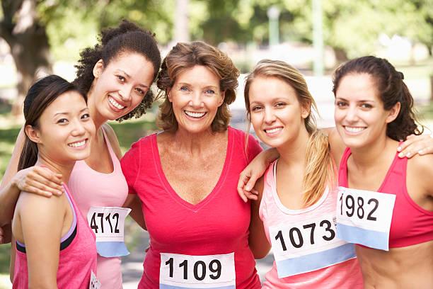 gruppe von weiblichen athleten, die an charity-marathon - rosa training stock-fotos und bilder