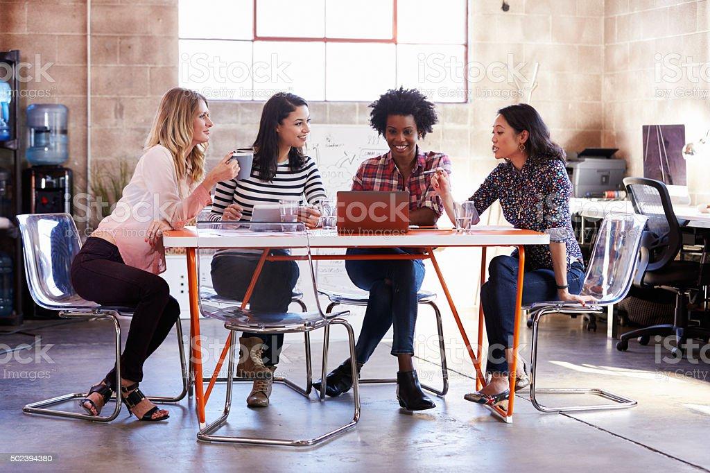 Grupo de diseñadores que hembra de reunión en oficina moderna - foto de stock
