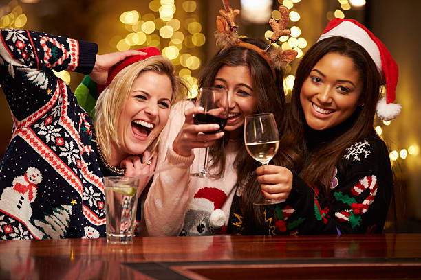 gruppe von freundinnen genießen sie weihnachten getränke in der bar - bier kostüm stock-fotos und bilder