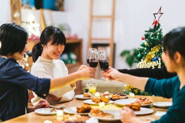 gruppe von freundinnen, die weihnachtsfeier zu hause genießen - weihnachten japan stock-fotos und bilder