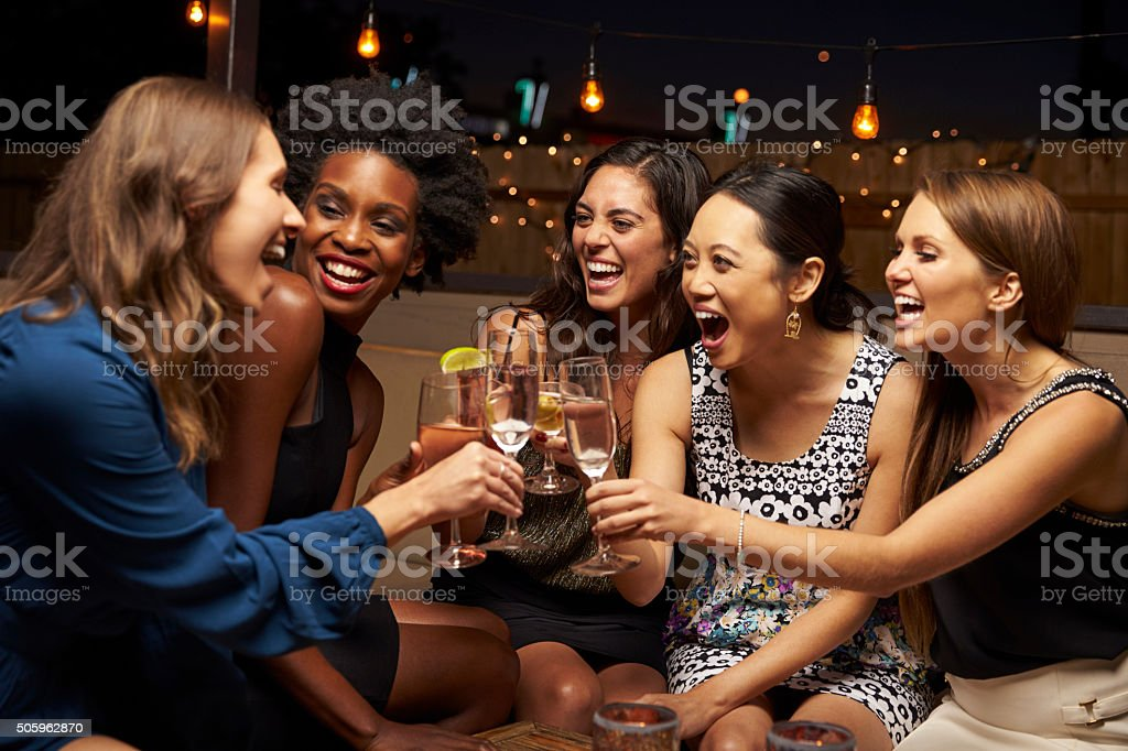 Group Of Female Friends Enjoying Night Out At Rooftop Bar stock photo