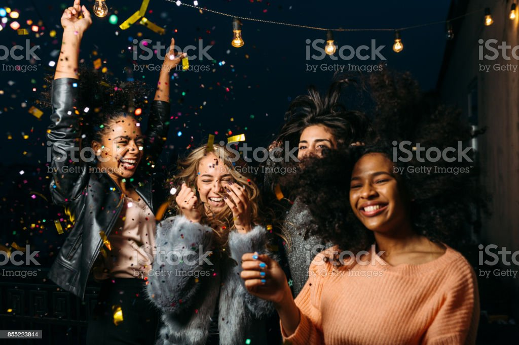 Group of female friends enjoying night party, throwing confetti stock photo