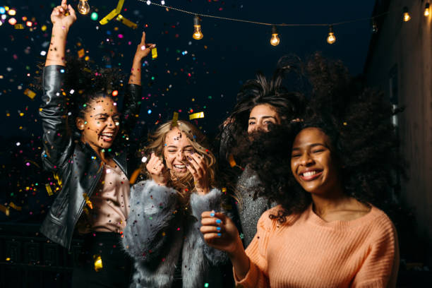 group of female friends enjoying night party, throwing confetti - girls party zdjęcia i obrazy z banku zdjęć