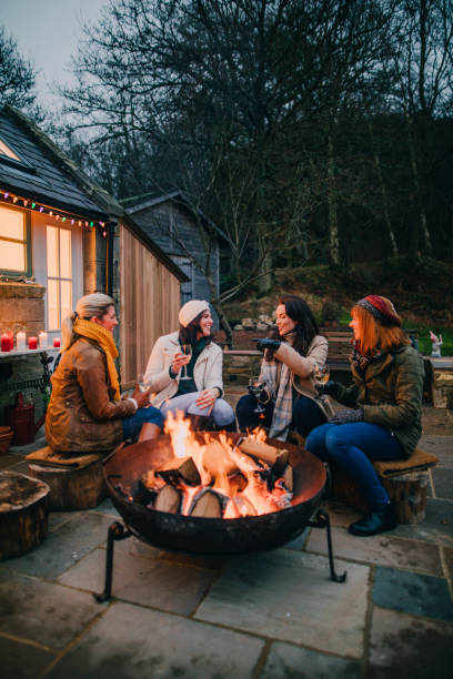Group of Female Friends Gathered Around a Fire Pit stock photo