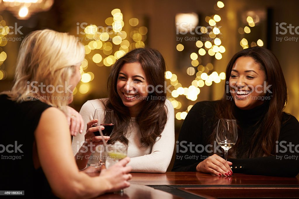 Group of female friends laughing over drinks at a bar stock photo
