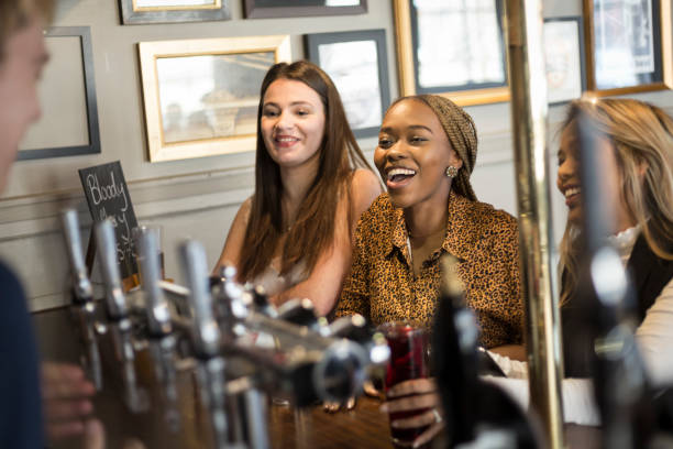 A group of female friends ordering drinks at a bar stock photo
