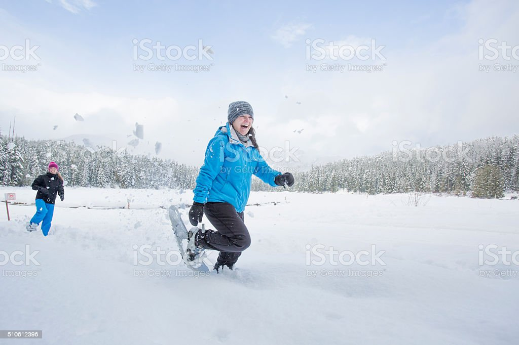 Group of female friends snowshoeing and having snowball fight. stock photo