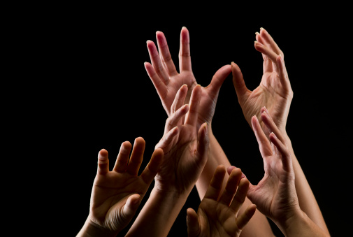 Female hands reaching out on black background