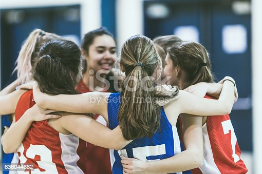 istock Group of female high school basketball players encouraging one another 636044662