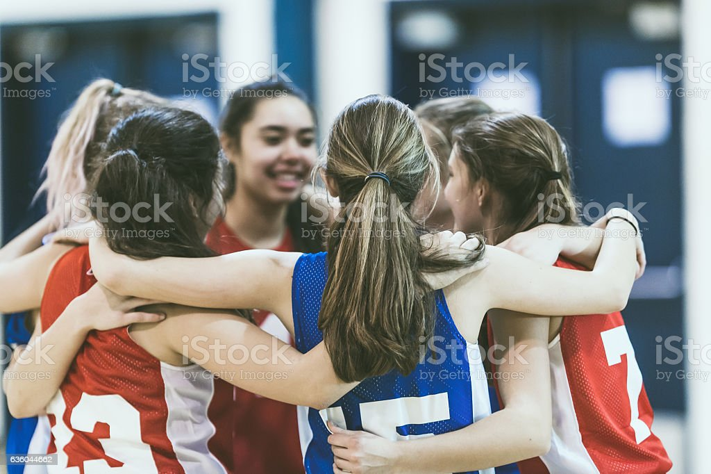 Group of female high school basketball players encouraging one another stock photo