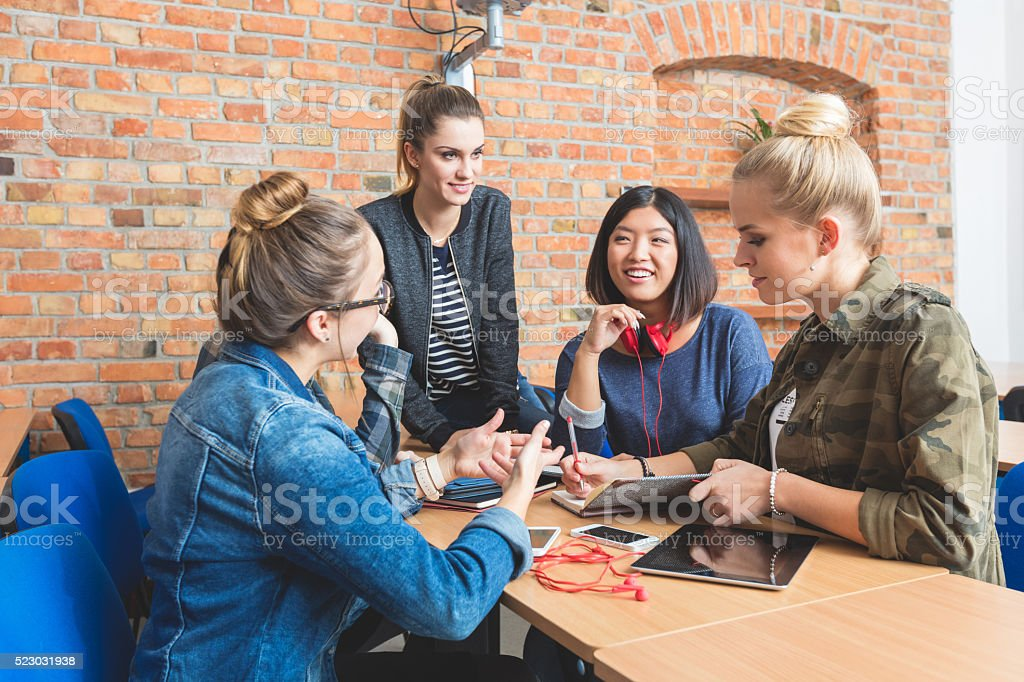 Group of female studens working together Group of female studens working together, discussing, laughing. Adult Stock Photo