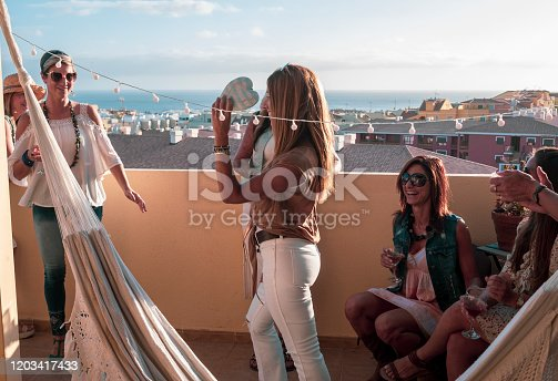 1016084100istockphoto A group of females in friendship celebrate the party by dancing. In the hands the glasses with wine to celebrate a special occasion. Sunset on the terrace overlooking the sea 1203417433