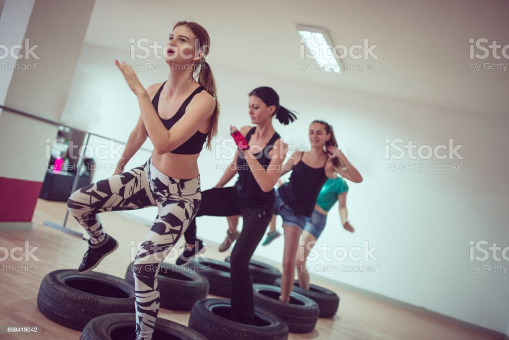 Group Of Females Receiving Tire Opstacle Cours Training in Gym stock photo