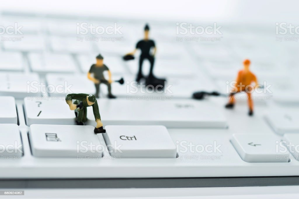 A group of figurines cleaning computer keyboard stock photo
